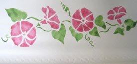 Pink flowers stenciled on a vinyl roller shade.